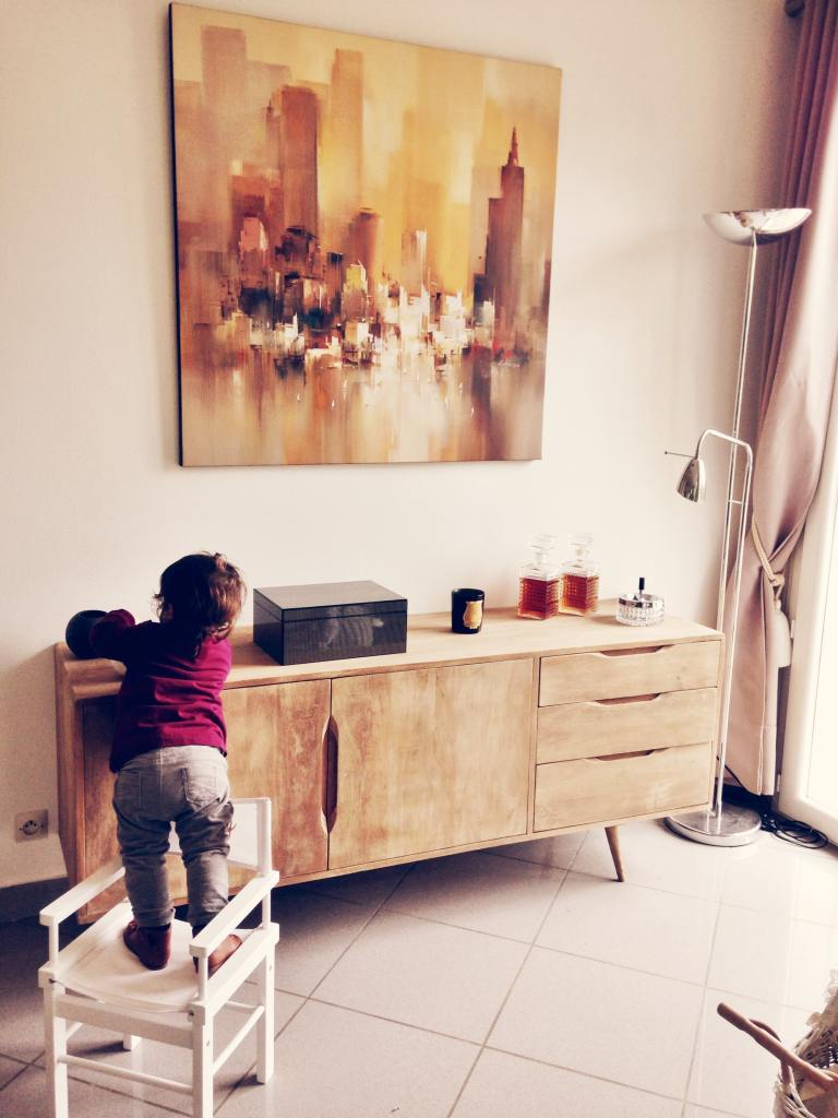 Toddler climbing on a chair to reach an object on a bench