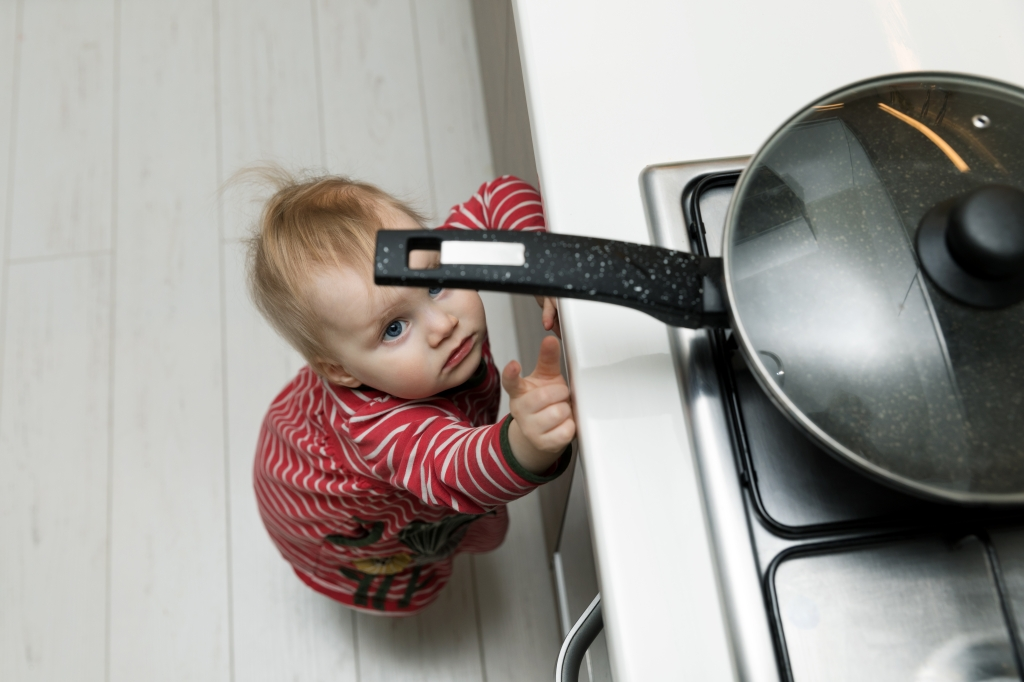 Toddler reaching for a pan on the stove in kitchen