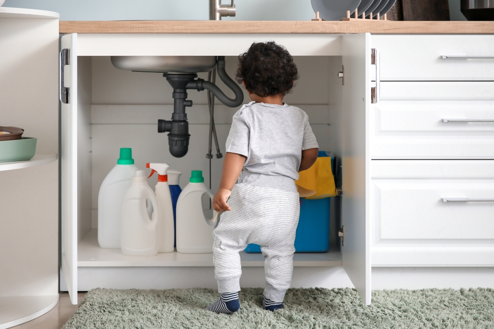 Toddler dangerously playing with chemicals under the sink