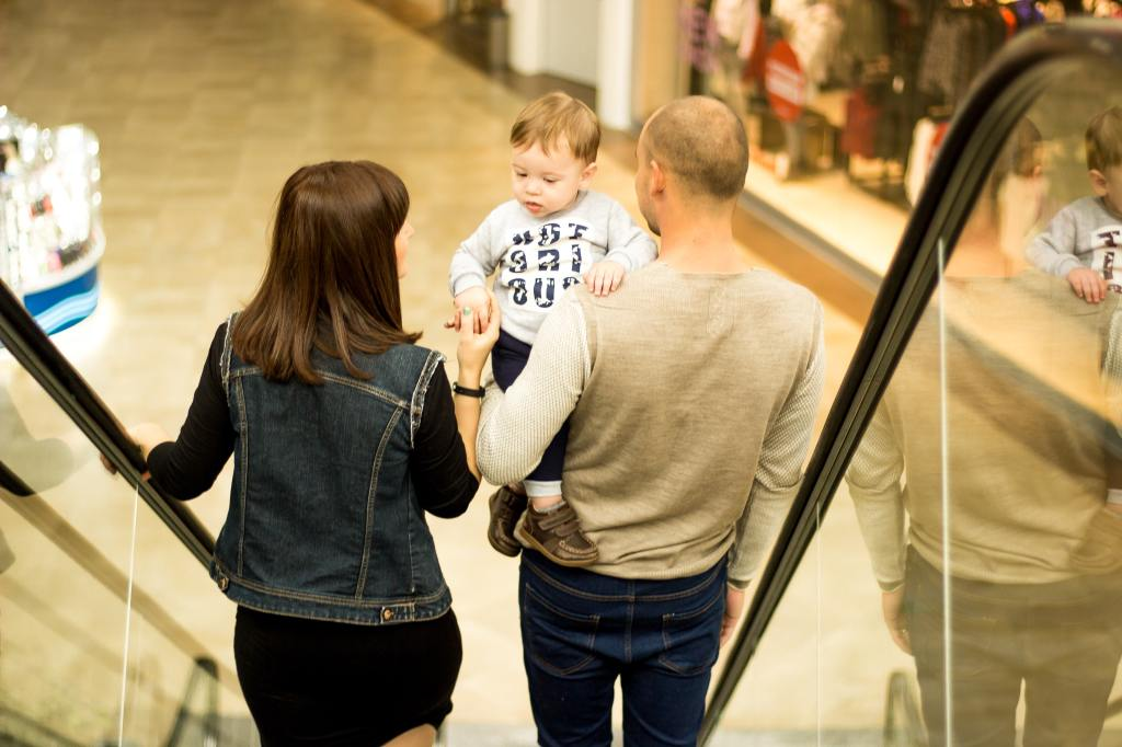 Mummy and daddy carrying toddler on moving escalator
