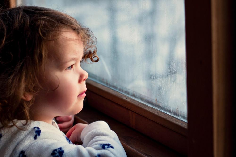 Child looking outside a window