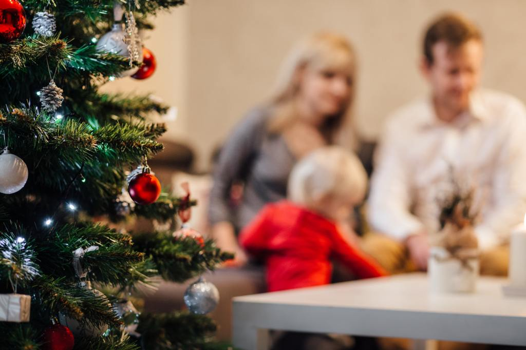 Mum, dad and toddler sitting next to a Christmas tree