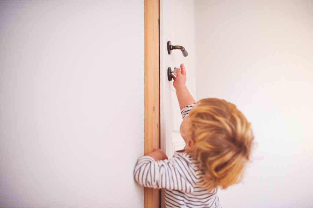 Toddler trying to lock the door using a key