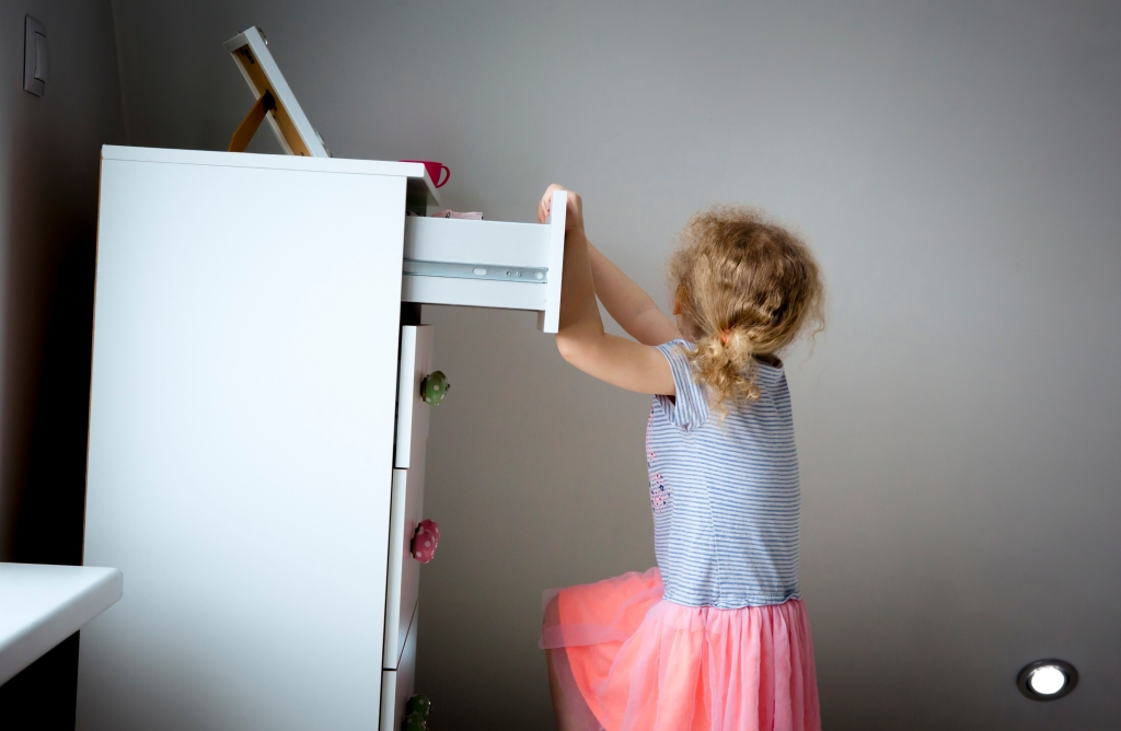 Child dangerously climbing a dresser  on the verge of tip-over