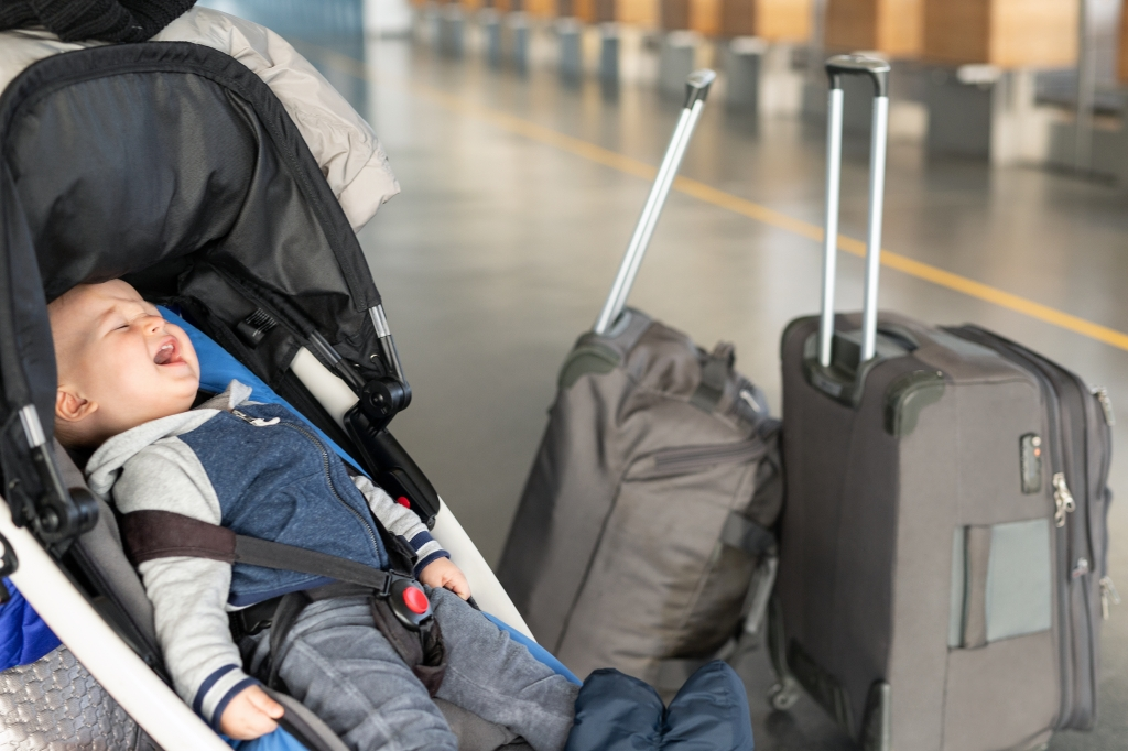 Screaming toddler sitting in his stroller near luggage at airport terminal