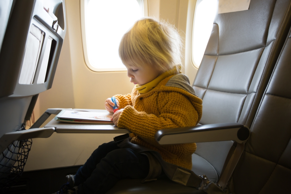 Blonde toddler boy, flying with airplane and entertained with book coloring