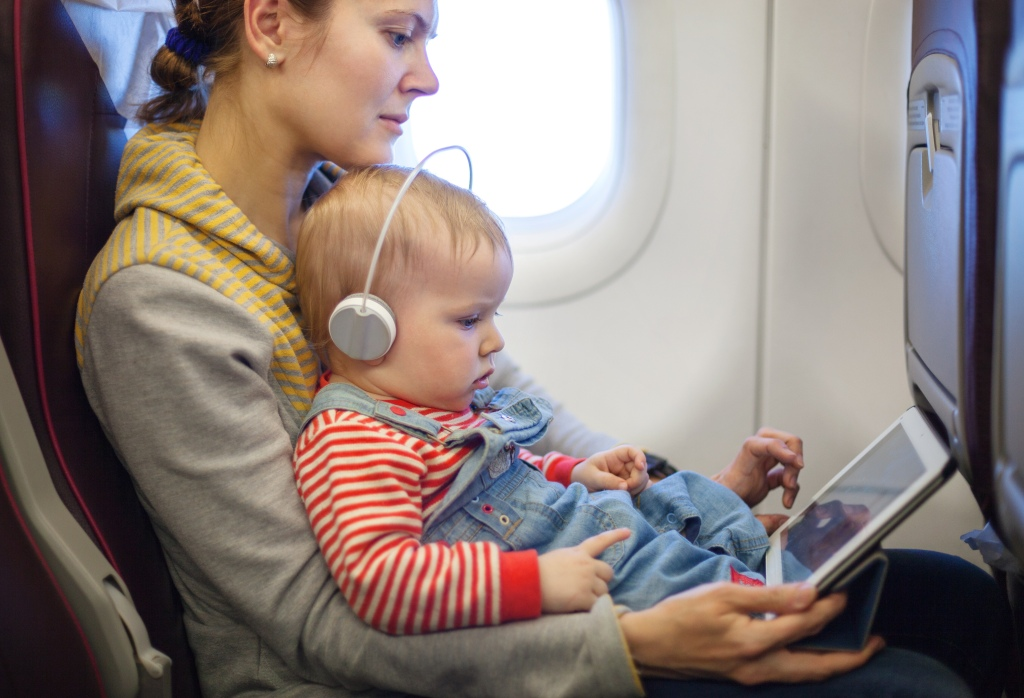 Mother and toddler son using tablet  while on board of an airplane