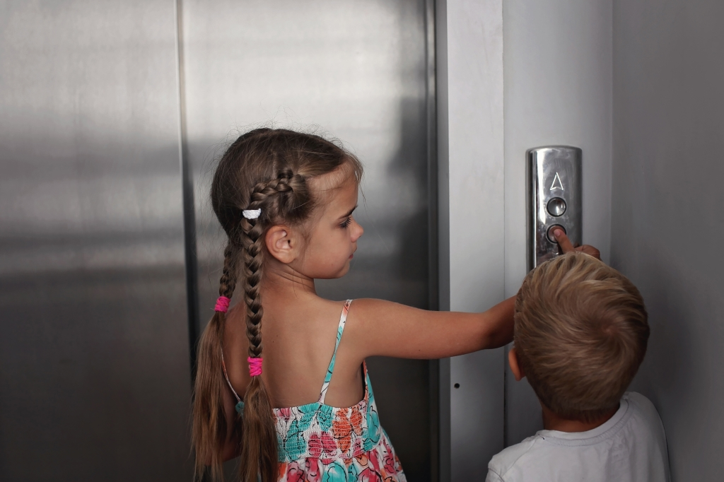 Children inside the lift pressing an elevator button